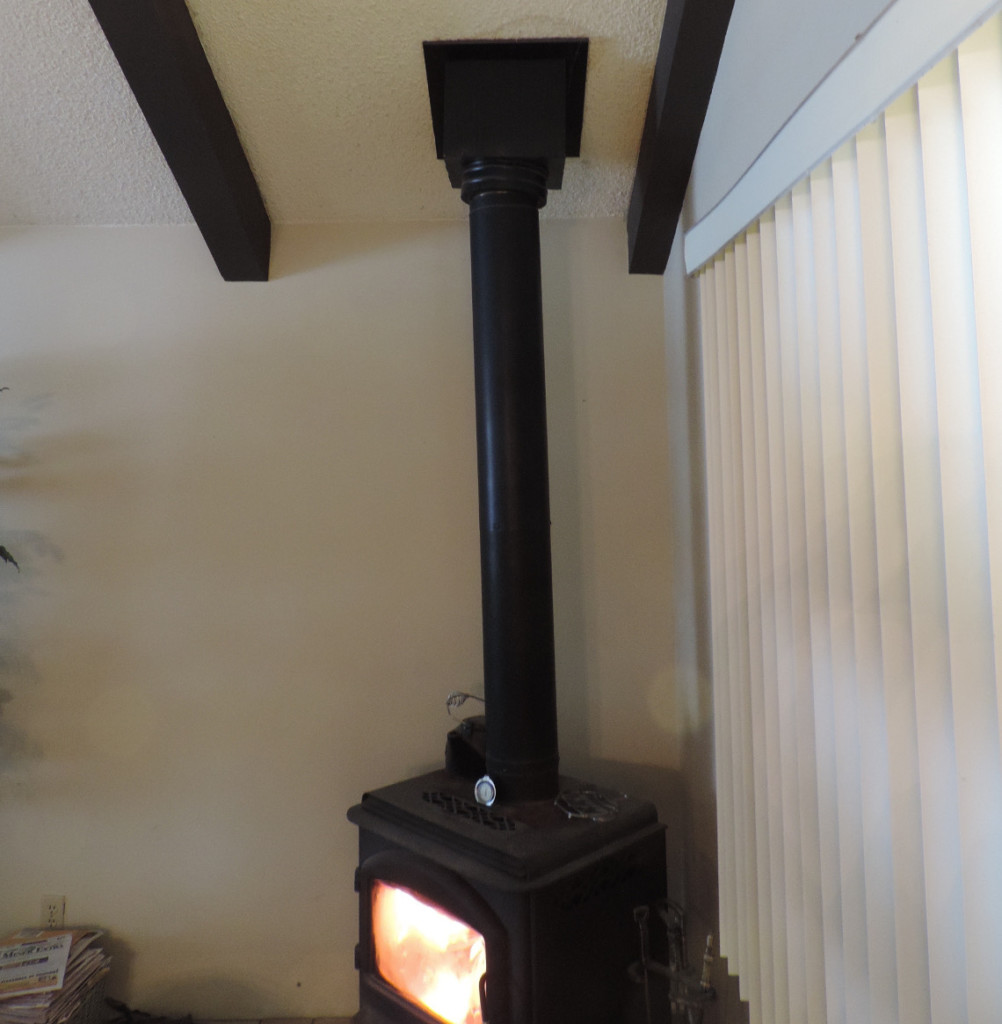 Wood stove with black double walled chimney pipe