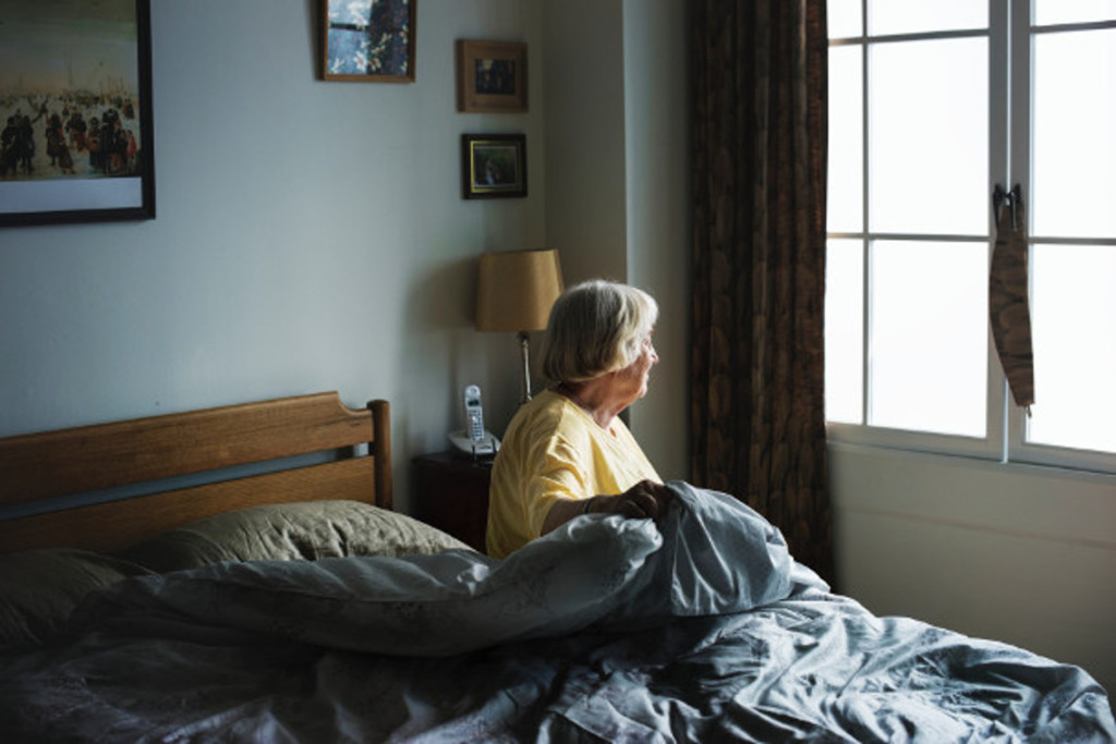 lady sitting on bed lookikng out window