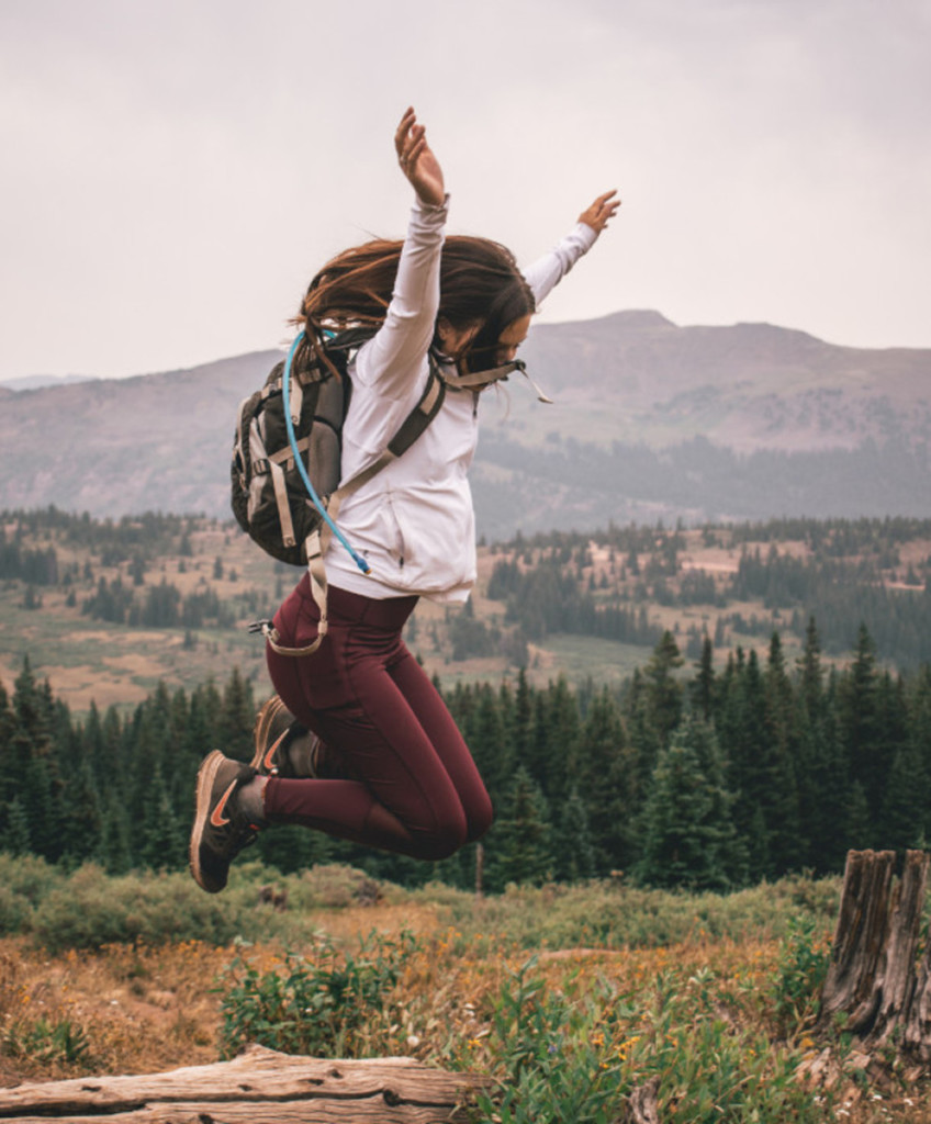 girl jumping in the air with backpack on