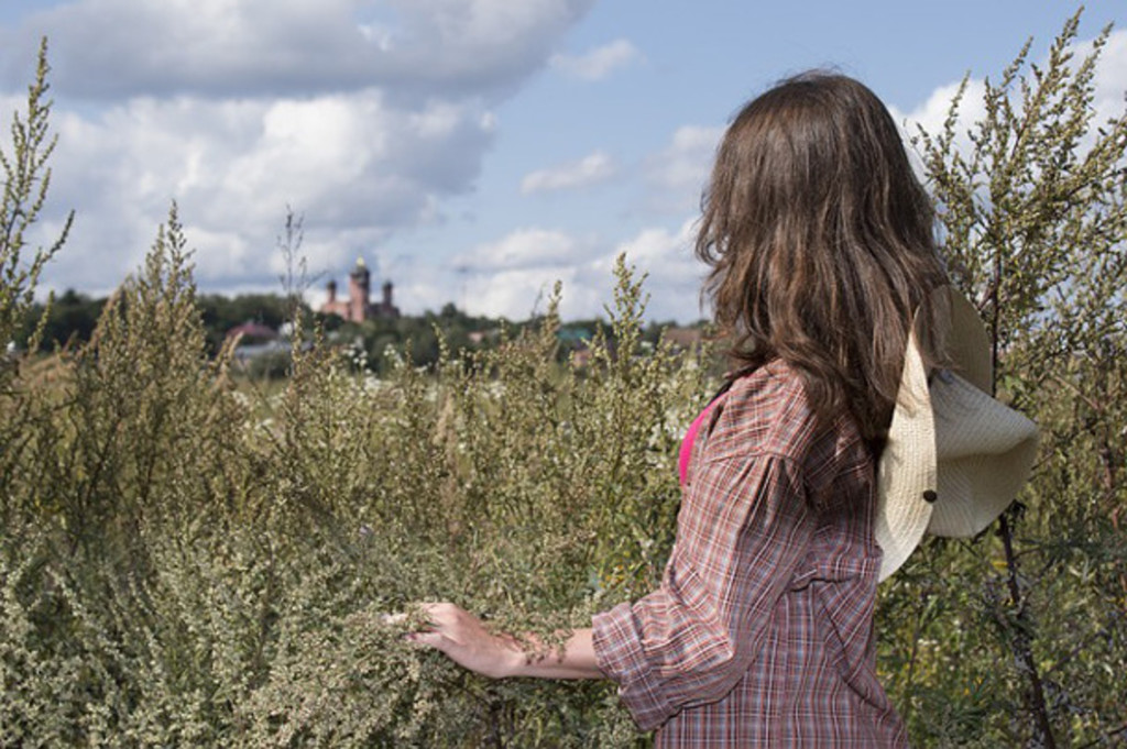 girl with long hair looking across a field