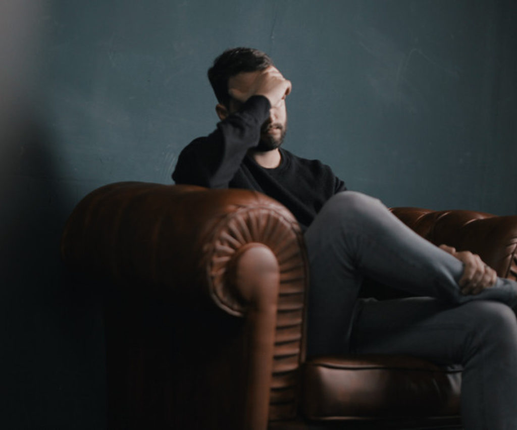 man sitting in chair with head in his hand
